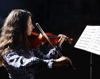 Beautiful violinist musician with sheet music on a stand on black background