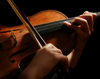 Violin is in the hands of professional violinist. Details of violin playing isolated on black background