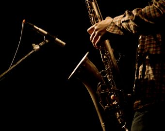 Warm photo of the male saxophonis playing in sax