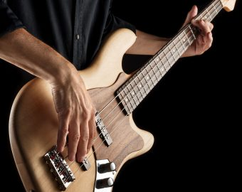 bassist playing an electric bass guitar on black background